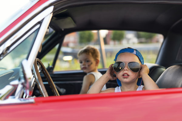Kids driving in the front seat with shades