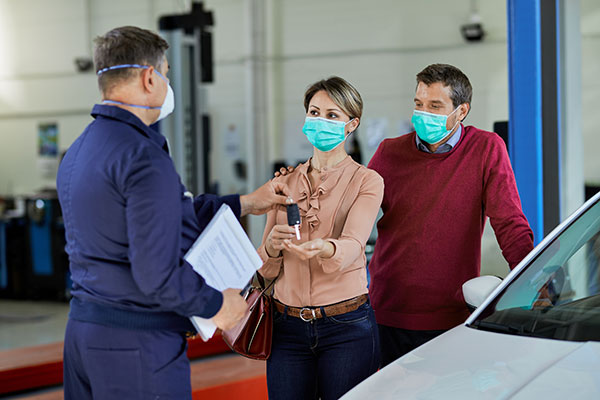 after a summer car service the mechanic hands back the keys to customers wearing safety masks