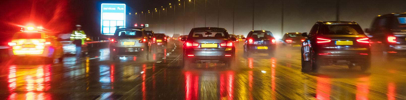 Window screen view of traffic ahead on a rainy motorway