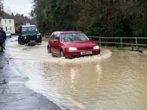 After the rain, cars have to drive carefully in flooded areas